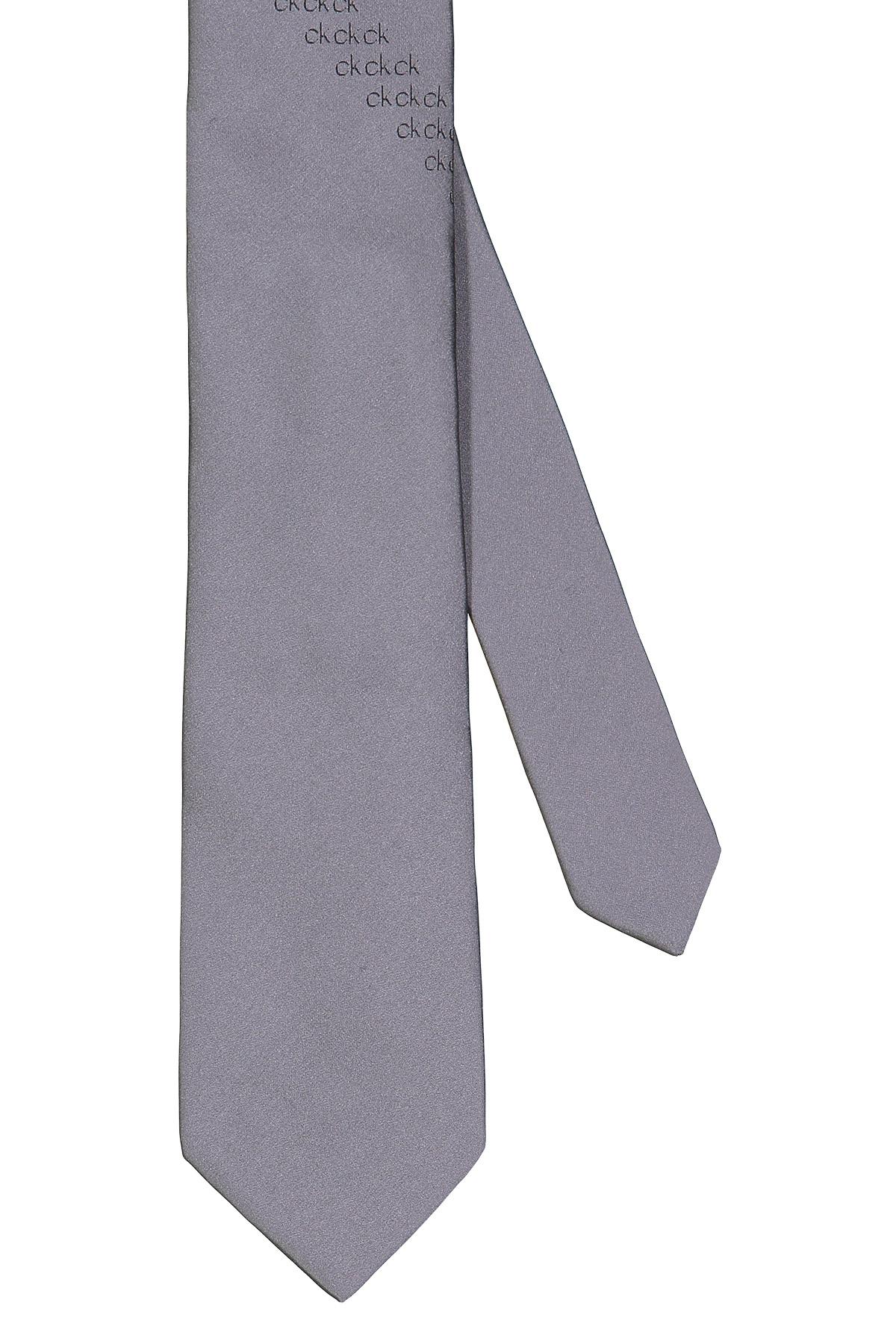 Corbata Calvin Klein, 100% seda, lisa gris con bordado en centro.
